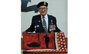 Charlie Fielding holds his quilt presented to him by Quilts of Valour Legion on July 12.